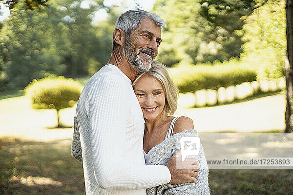 Happy mature couple hugging in backyard