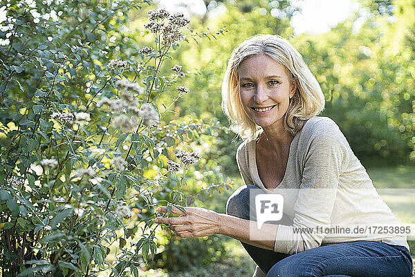 Portrait of smiling mature woman touching plant in backyard