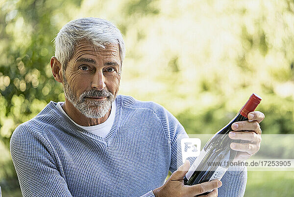 Portrait of mature man holding wine bottle while sitting on chair
