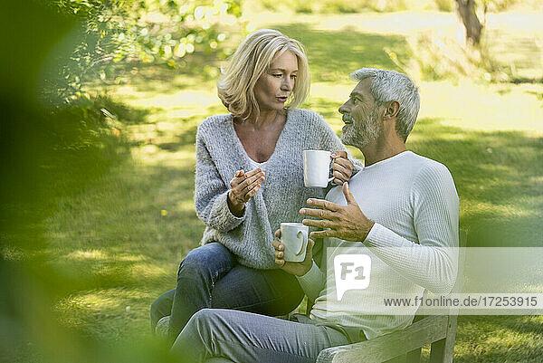 Mature couple talking while having coffee in backyard