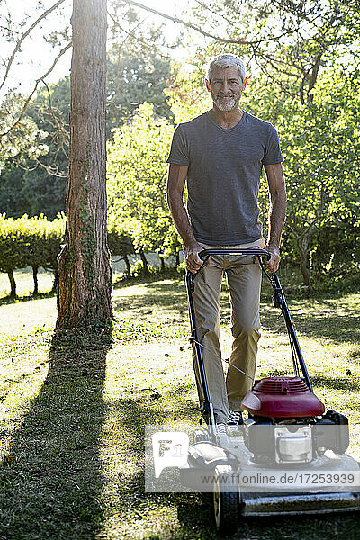 Portrait of smiling mature man mowing grass with mower