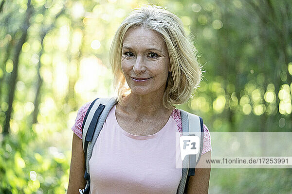 Portrait of smiling mature woman standing in forest