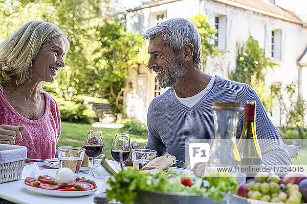 Smiling mature couple looking at each other while enjoying meal in backyard