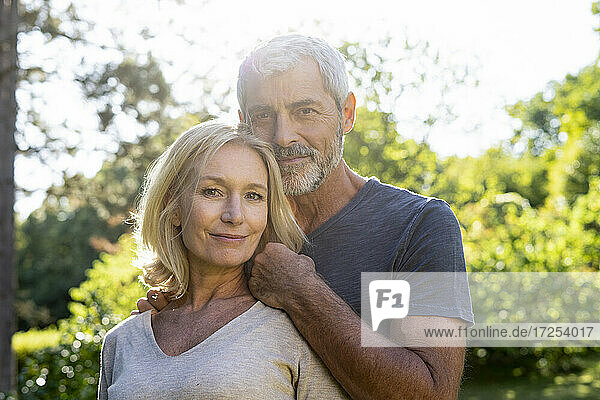 Portrait of smiling mature couple standing in backyard