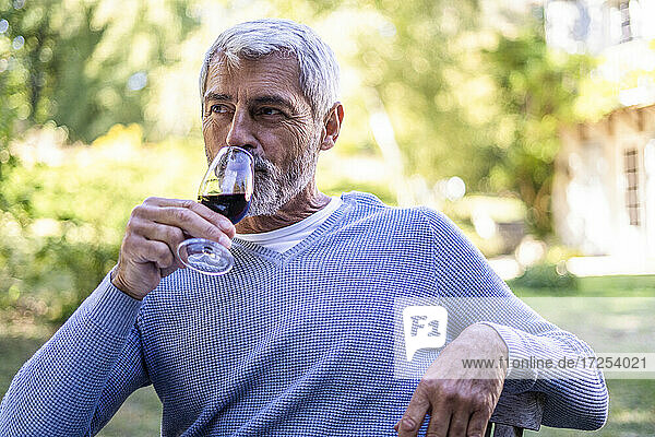 Mature man drinking red wine while sitting on chair