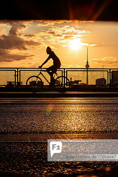 Silhouette of man cycling on bridge with Fernsehturm Berlin in background during sunset