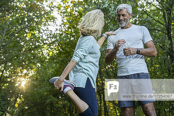 Low angle view of smiling mature couple talking while exercising in forest