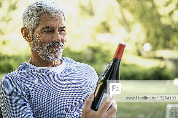 Smiling mature man looking at wine bottle while sitting on chair