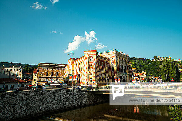 Exterior view of Sarajevo City Hall and bridge against sky