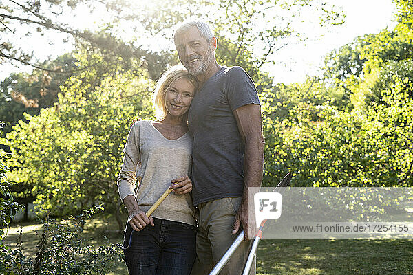 Portrait of mature couple standing in backyard