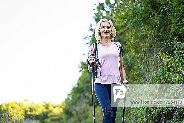 Low angle view of smiling mature woman hiking in forest