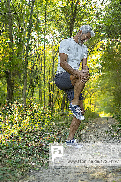 Mature man suffering from knee pain while standing in forest