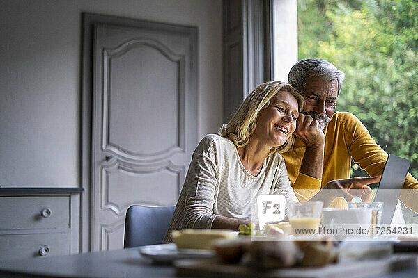 Lächelndes reifes Paar benutzt Laptop zu Hause
