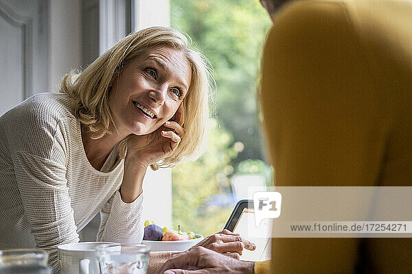 Smiling mature woman looking at her husband while using digital tablet