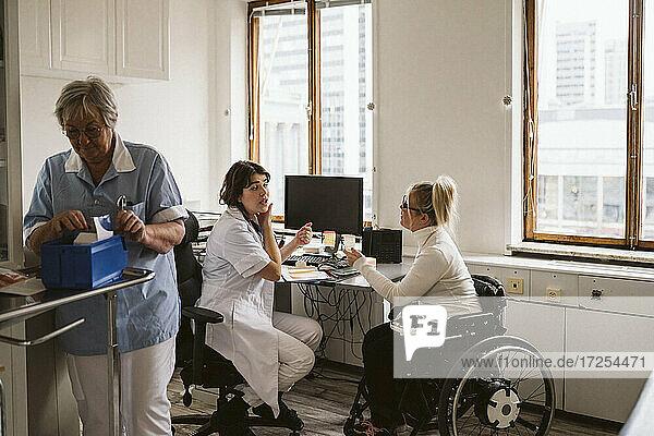 Weiblicher medizinischer Experte im Gespräch mit einem behinderten Patienten  während die Oberschwester arbeitet