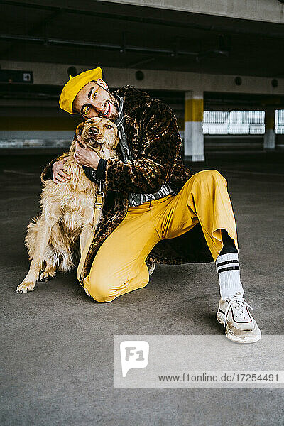 Junger Mann umarmt Hund im Parkhaus in voller Länge