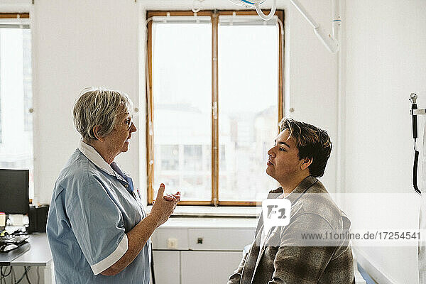 Senior medical expert discussing with male patient while consulting in clinic