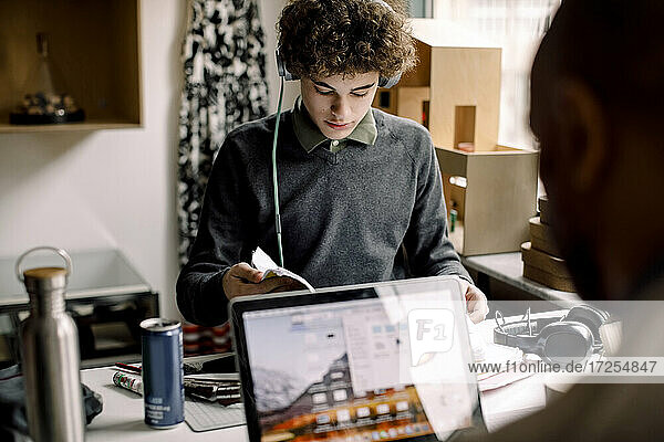 Teenage boy studying while father working on laptop at desk