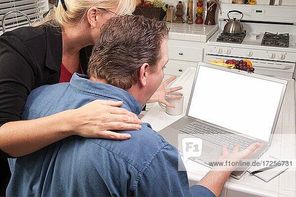 Ehepaar in der Küche mit Laptop mit leerem Bildschirm