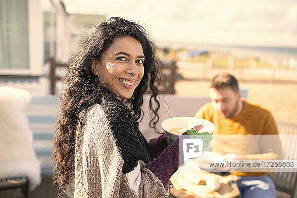Portrait happy woman eating on sunny patio