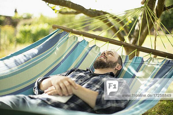 Serene Mann entspannt in sonnigen Sommer Hängematte
