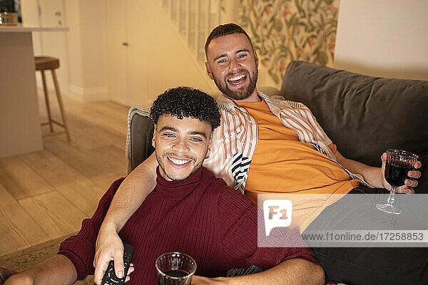Porträt glücklich Homosexuell männliches Paar trinken Wein auf Sofa zu Hause