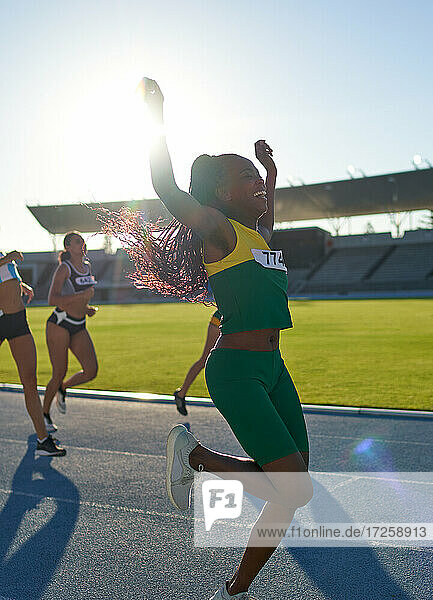 Happy female track and field athlete winning race on sunny track