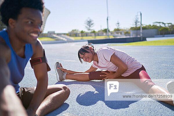 Glückliche junge Läufer beim Dehnen auf der sonnigen Sportbahn