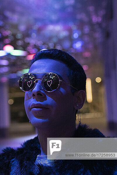 Reflexion von Neon Herz in Sonnenbrille von jungen Mann in der Stadt in der Nacht