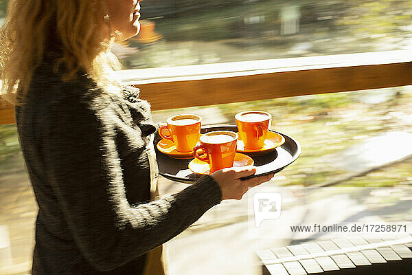 Weibliche Barista trägt Tablett von Kaffeetassen entlang sonnigen Café Fenster