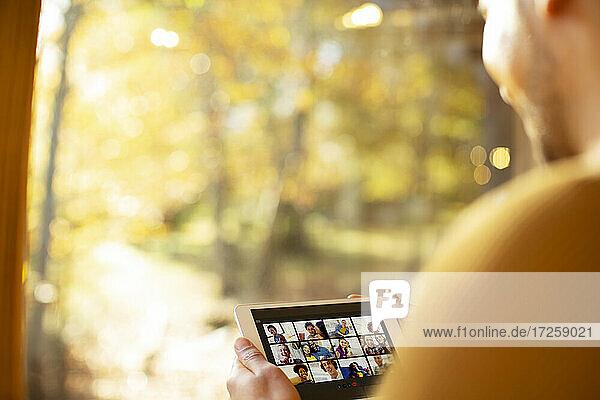 Mann Video-Chat mit Freunden auf digitalen Tablette an sonnigen Fenster