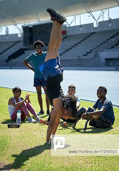 Athletenfreunde beobachten jungen Mann beim Handstand im Stadion