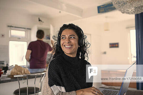 Happy woman with headphones working from home at laptop
