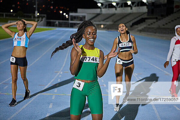 Happy female track and field athlete celebrating after race on track