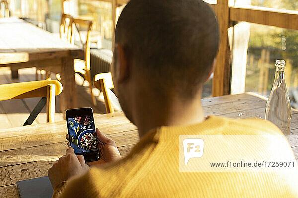Männlicher Geschäftsinhaber  der sich die Speisekarte eines Restaurants auf einem Smartphone ansieht