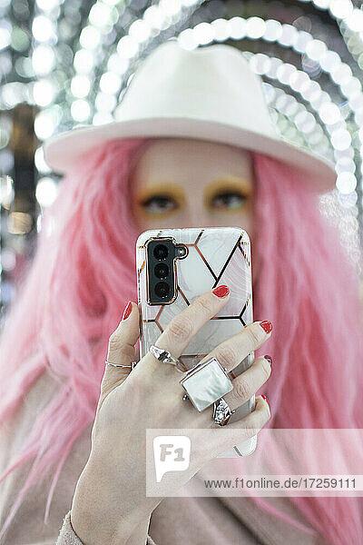 Porträt schöne Frau mit rosa Haaren nehmen selfie mit Smartphone