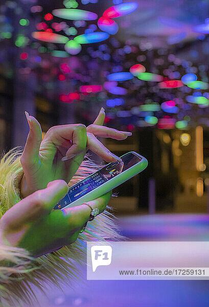 Close up Frau mit Smartphone in Nachtclub unter Neonlicht