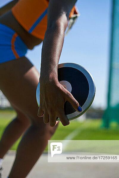 Weibliche Leichtathletin beim Diskuswurf
