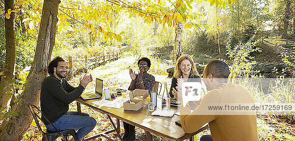 Happy business people clapping and meeting in sunny autumn park