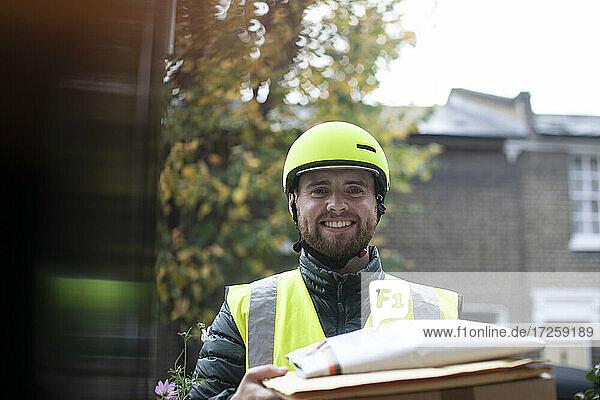 Portrait friendly delivery man in helmet delivering packages at door