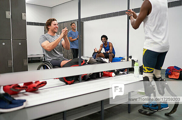 Happy amputee and wheelchair athletes clapping in locker room