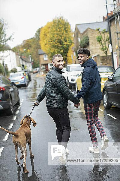 Porträt glücklich Homosexuell männliches Paar zu Fuß Hund auf nassen Herbst Straße