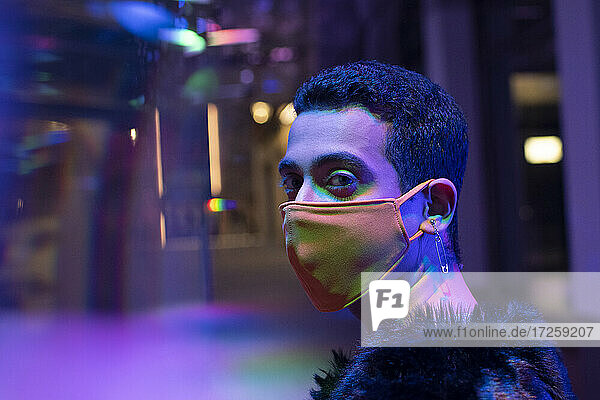Portrait stylish young man with safety pin earrings wearing face mask