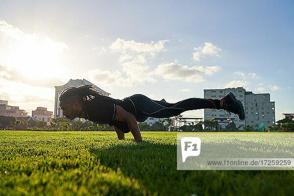 Athletischer junger Mann trainiert im sonnigen Stadtpark
