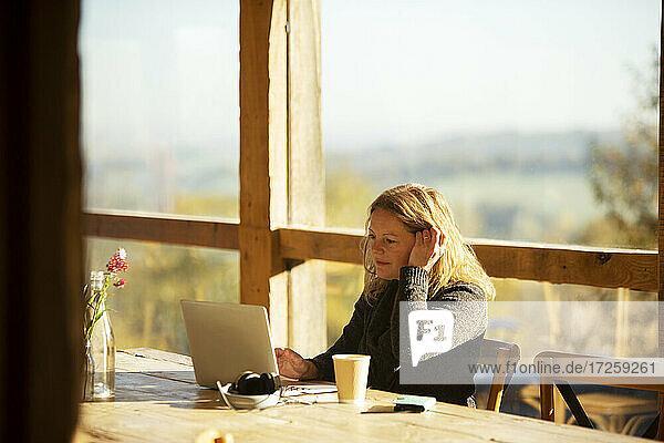 Geschäftsfrau arbeitet am Laptop an sonnigen Café Tisch