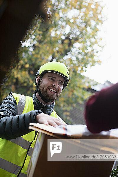 Freundlicher Zusteller mit Helm  der Pakete an der Tür abliefert