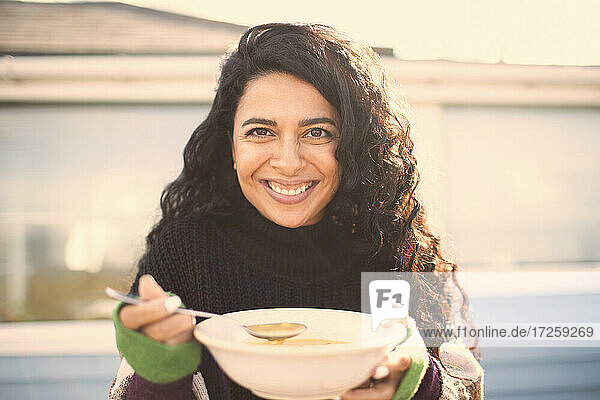 Porträt schöne glückliche Frau essen chowder auf sonnigen Terrasse