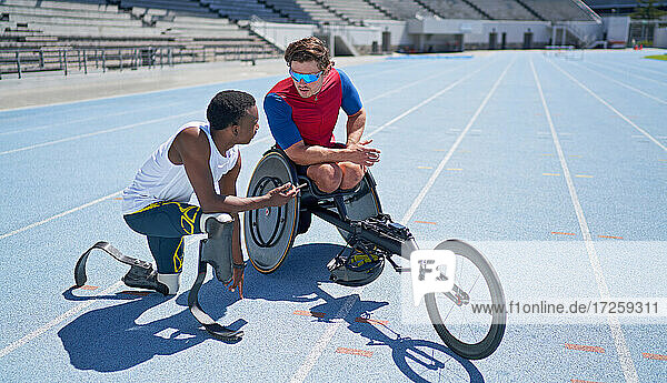 Male amputee and wheelchair athletes talking on sunny blue track