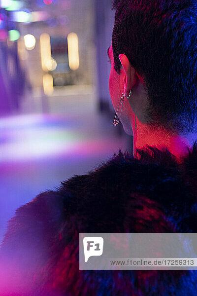 Stilvoller junger Mann mit Sicherheitsnadel-Ohrring auf dem Gehweg