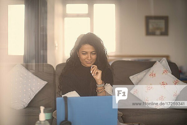 Woman working from home at laptop in living room